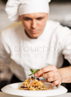 Chef decorating pasta salad with herbal leaves