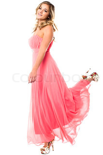 Charming girl in strapless party dress lifting leg