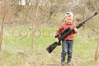 Small boy carrying a rifle