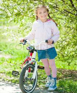 Portrait Of Little Girl On A Bicycle In The Park Stock