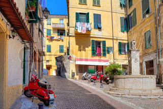 Typical view of small cobblestone street with scooters among old colorful residential buildings in town of Ventimiglia, Italy.