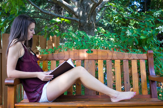 Pretty teen girl reading outside on a bench - copyspace