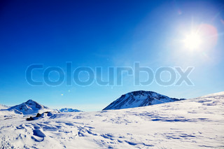 Snow mountains, blue sky and sun in East Greenland