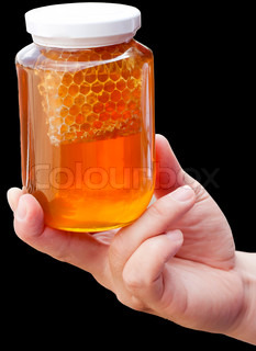 Natural floral honey in hand isolated on a black background