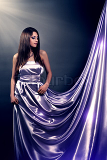 Beautiful girl in violet long dress on black background