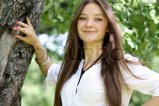 Happy young beautiful girl standing near tree