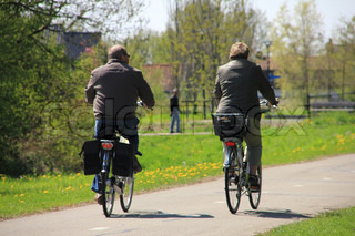 Walking man, a retired couple are biking, having fun in their spare time in the open air in spring.