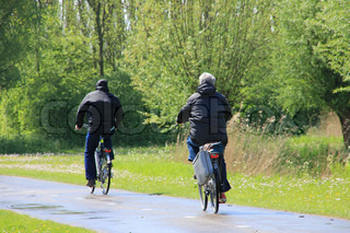 Retired couple with rain gear biking on the wet bike path and trees along the way and  going home.
