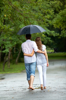 back view of woman and man walking under umbrella during