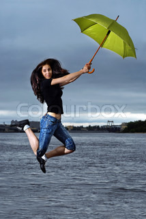 girl jumping against sky and water with umbrella