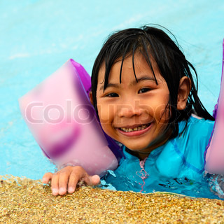 Photo of happy girl in pool smiling at camera