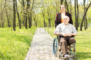 Wife walking a disabled man in a wheelchair
