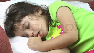 A close up of a beautiful little girl sleeping peacefully.