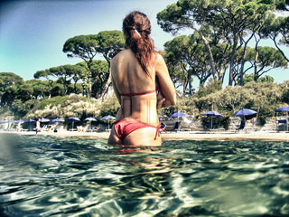 Back view of a Woman making a Bath in Tuscan Sea