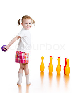 Kid girl throwing ball to knock down toy bowling pins Focus on child