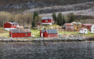 Traditional Norwegian small village with red wooden houses on rocky coast in spring