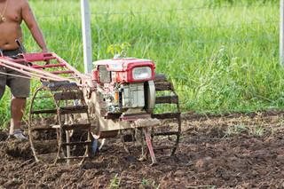 Thai farmer on small tractor
