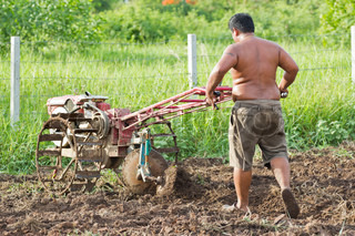 Thai farmer on small tractor