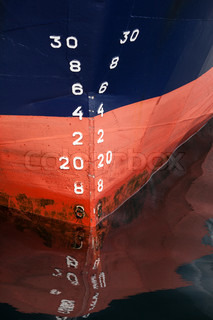 Bow of the cargo ship with red waterline and draft scale numbering