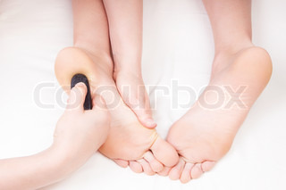 Therapist doing a foot massage, pressing reflexology zone on woman's heel with a hot stone