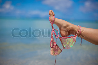 Woman leg hold pink bra isolated on exotic background