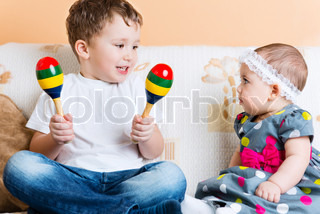 Cute little sister and her brother sitting with maracas