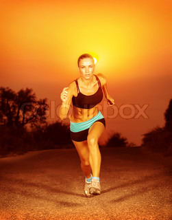 Sporty woman running on sunset