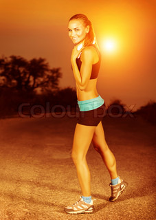 Happy sporty woman doing exercise at sunset, fitness outdoors, open air workout, loss weight, perfect muscular body, healthy lifestyle concept