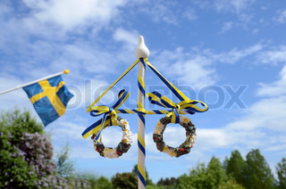 Maypole and Swedish flag against a blue sky