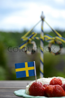 Strawberries and cream on a table with a maypole
