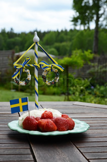 Strawberries and cream with a Swedish flag in the background is a maypole