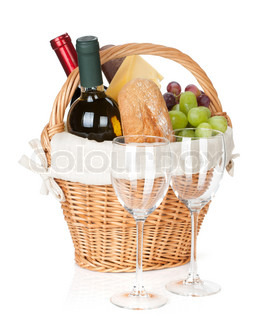 Picnic basket with bread, cheese, grape and wine bottles