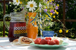 Coffee and juice served, on a table in a pergola in the garden