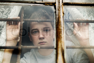 The boy looks out of the window through a lattice