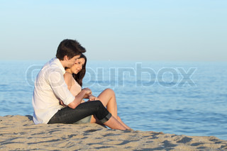 Couple hugging sitting on the sand of the beach