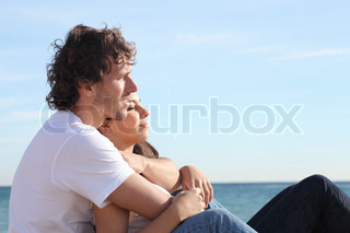 Man and woman couple hugging on the beach and flirting