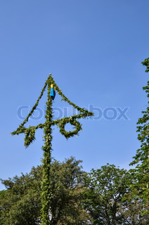 Swedish midsummer pole in a summer landscape with blue sky