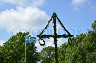 Swedish midsummer pole and swedish flag at green trees and blue sky.
