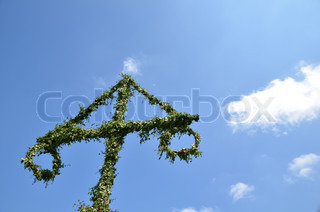 May pole , symbol for midsummer in Sweden, at a blue sky with white clouds