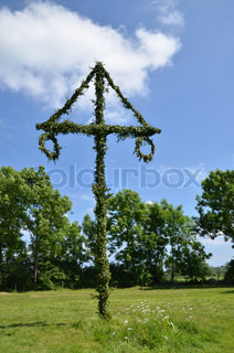Swedish midsummer pole in a summer landscape with blue sky and white clouds