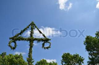 Midsummer pole at green trees and blue sky with white clouds.
