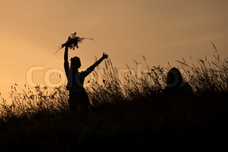 Silhouettes of girl picking flowers during midsummer soltice