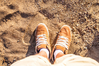 Pair of Boots Shoes man's Foot on a sand sea-side beach view from above Summer Leisure time background
