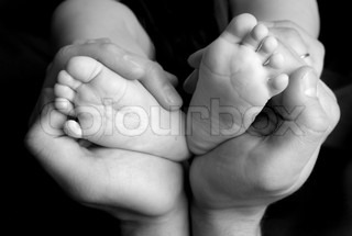 small baby's feet in daddy's hands on black