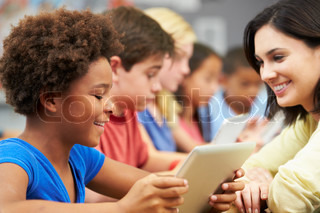 Pupils In Class Using Digital Tablet With Teacher