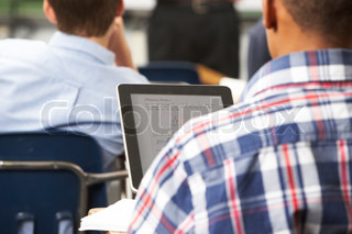 Male Pupil Using Digital Tablet In Classroom