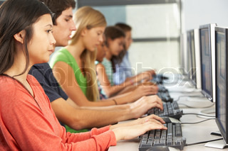 Group Of Students Working At Computers In Classroom