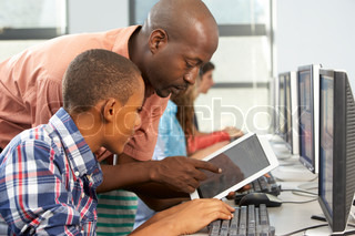 Teacher Helping Boy To Use Digital Tablet In Computer Class