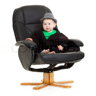 baby boy sits in office chair isolated on white background
