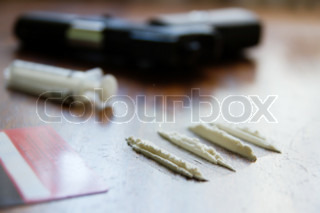 Lines of cocaine,syringe,gun on the background